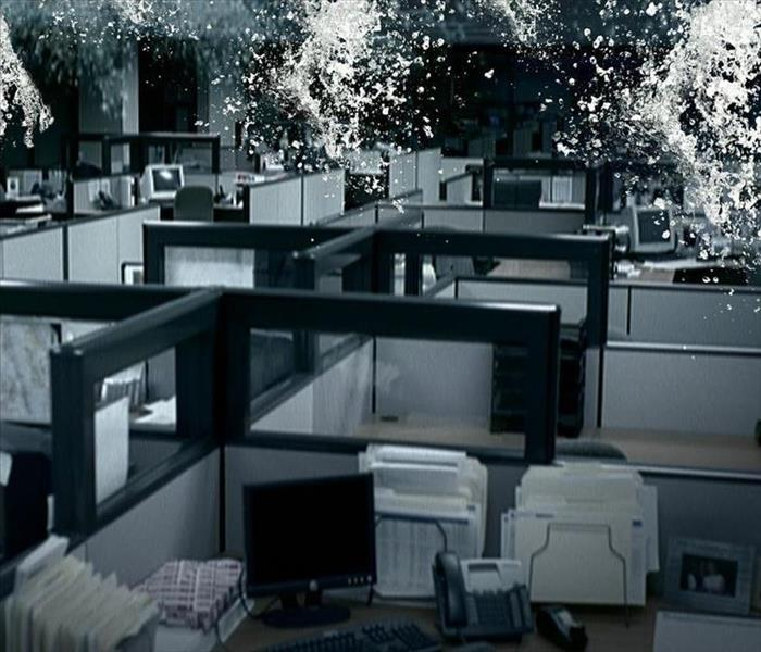 Water falling from the ceiling into a group of grey and white office cubicles