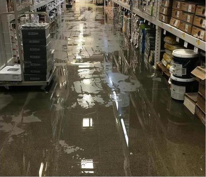 water on this commercial building floor with shelving on sides